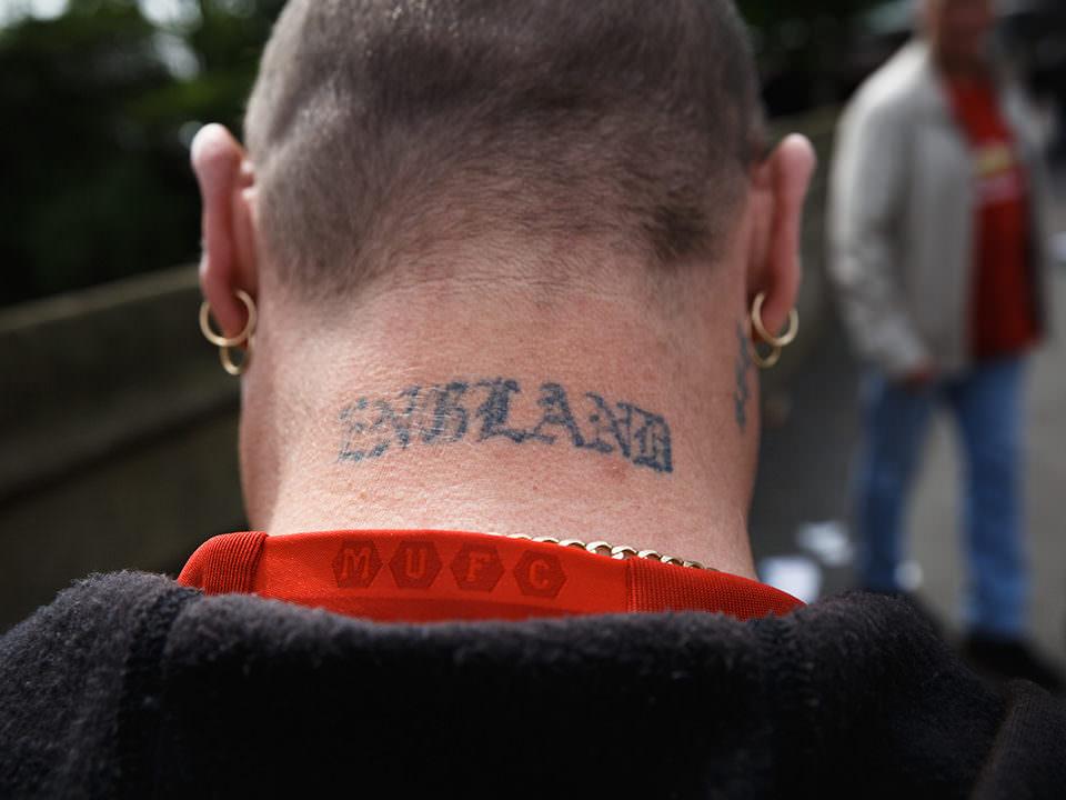 Der Nacken eines Mannes mit kurzen Haaren und England-Tattoo.
