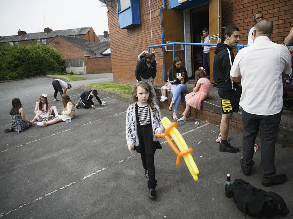 Menschen vor einem Haus. Dazwischen ein kleines Mädchen mit einer Luftballonwaffe.