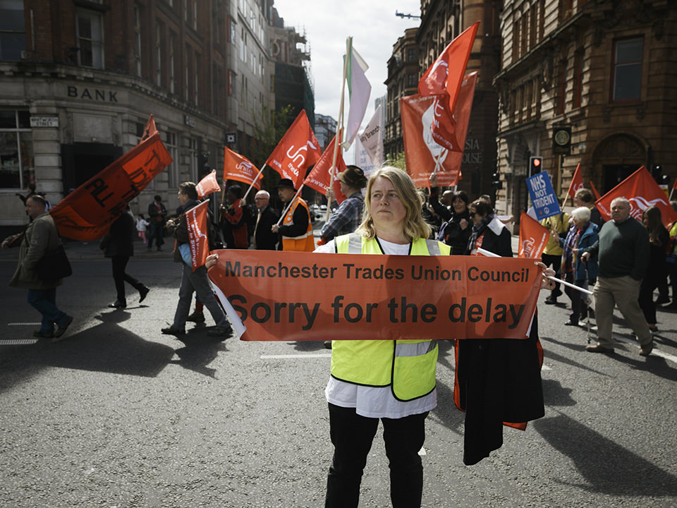 """Frau in Warnweste hält auf einer Demo ein oranges Banner auf dem """"Sorry for the delay"""" steht."""