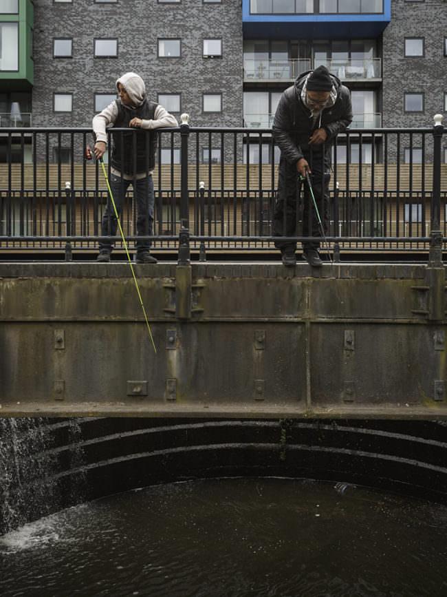 Zwei Angler stehen auf einer Brücke im städtischen Raum und angeln.
