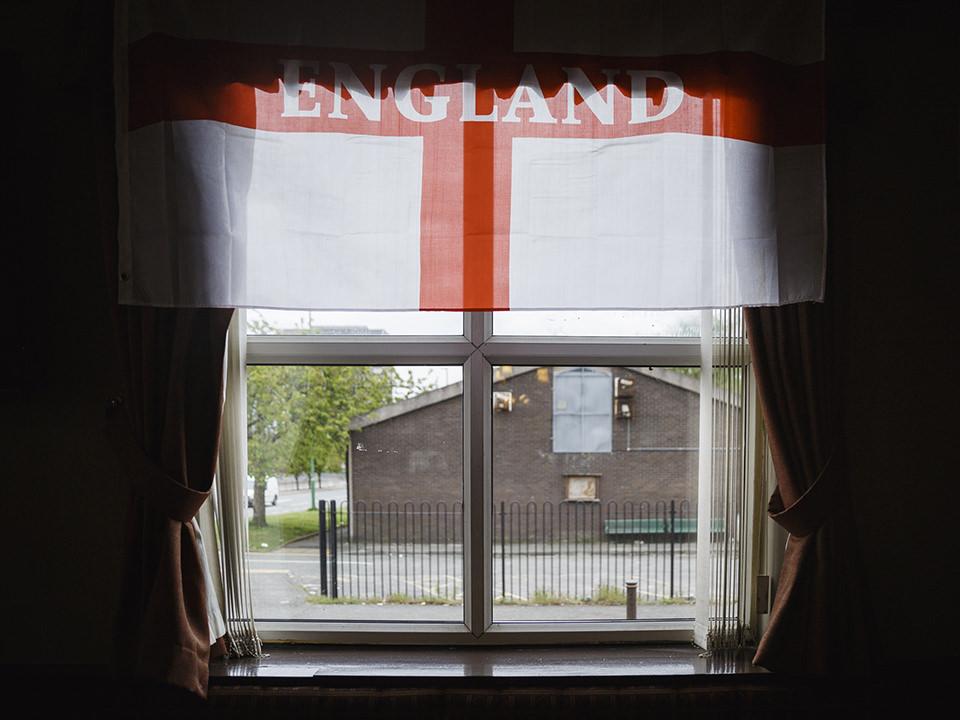 Von innen nach außen ein Blick durch ein Fenster, vor diesem hängt eine Englandfahne.