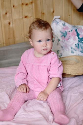 Ein kleines Kind in rosa Strumpfhose und Kleidchen sitzt auf einem Bett und blickt genau geradeaus.