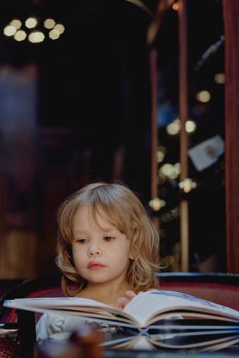 Ein kleines Kind mit langen blonden Haaren hat ein aufgeschlagenes Buch vor sich liegen, auf das es schaut.