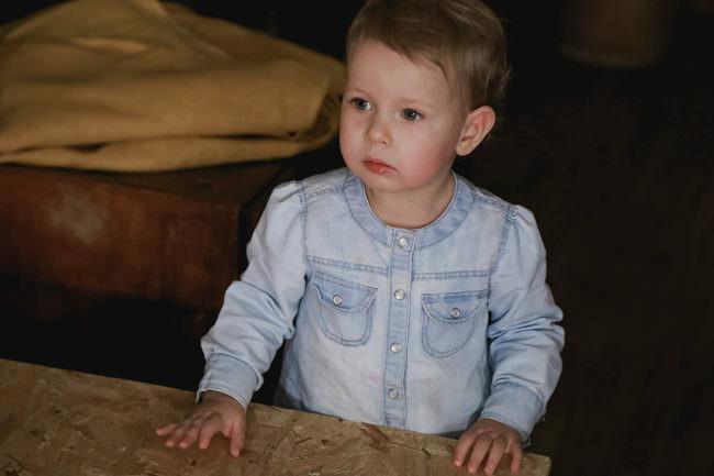 Ein kleines Kind steht neben einem Möbelstück auf das es die Hände gelegt hat und schaut nach links.