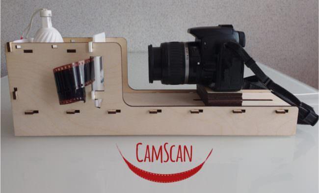 Eine Kamera, die auf einem Holzgestell befestigt ist und Negative abfotografiert.