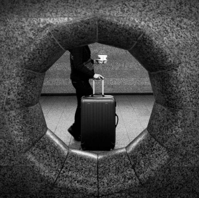 Blick durch ein Loch in der Wand auf einen Koffer