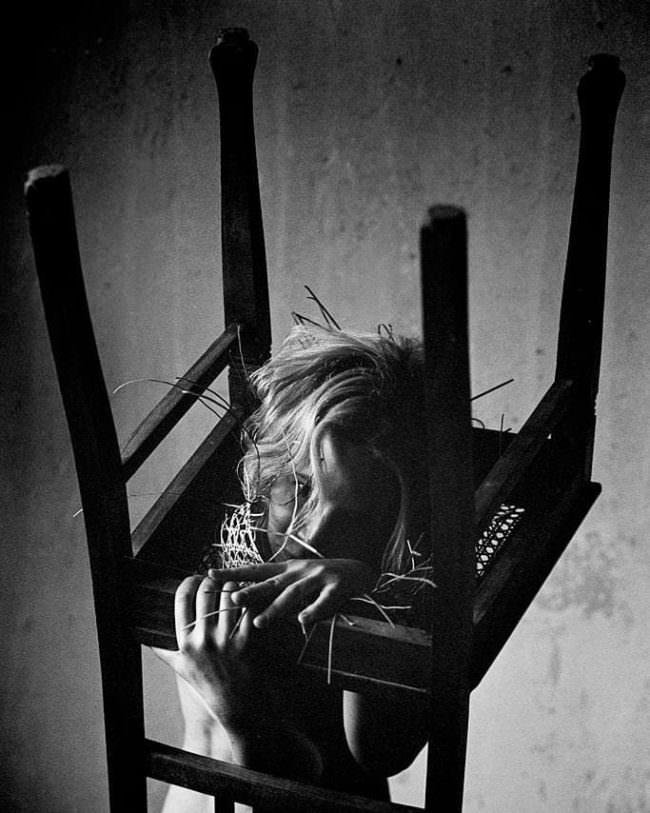 Eine Frau mit dem Kopf durch einen kaputten Stuhl