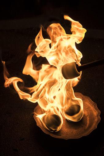 Schale mit brennen Bällen darin und orangen Flammen, die emporzüngeln.