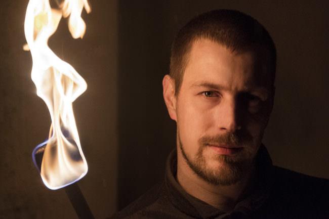 Portrait eines jungen Mannes, der nur von einer Flamme neben ihm beleuchtet wird.
