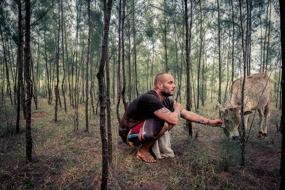 Mann mit Kuh im Wald