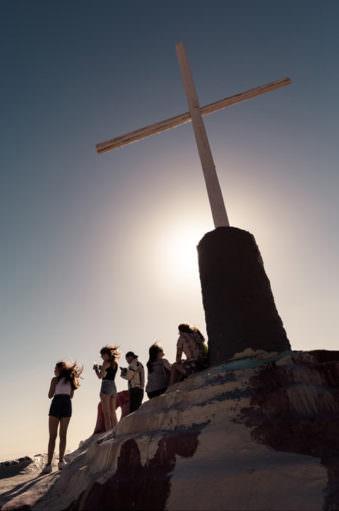 Menschen unter einem Gipfelkreuz