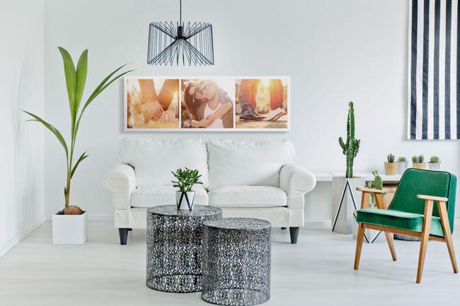 Wohnzimmer mit Sofa, Pflanzen und Designmöbeln sowie einem Triptychon von bunten Fotografien an der Wand.