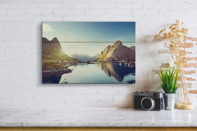 Wand mit Bild einer Berglandschaft auf Holz aufgebracht. Daneben angeschnitten eine Pflanze sowie eine Kamera auf einem Tisch.
