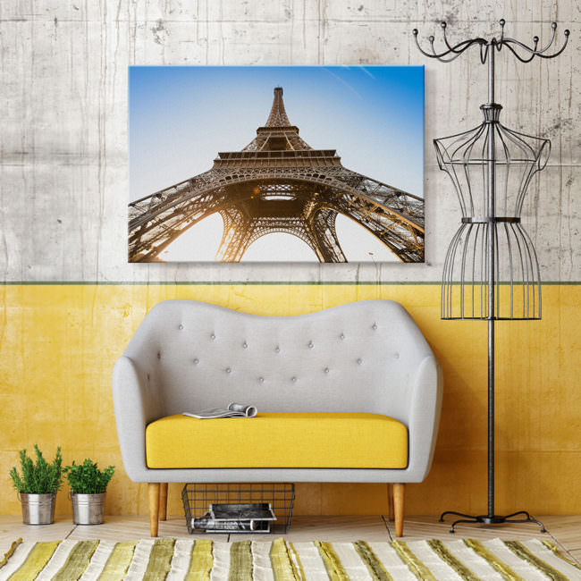 Innenraum mit Designermöbeln. Ein zweier Sofa, eine Modellpuppe als Garderobenständer und ein Bild an der Wand mit der Ansicht des Eifelturms von unten.