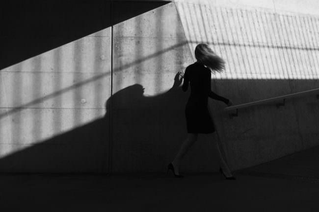 Eine Frau mit Lichtspielereien an einer Mauer