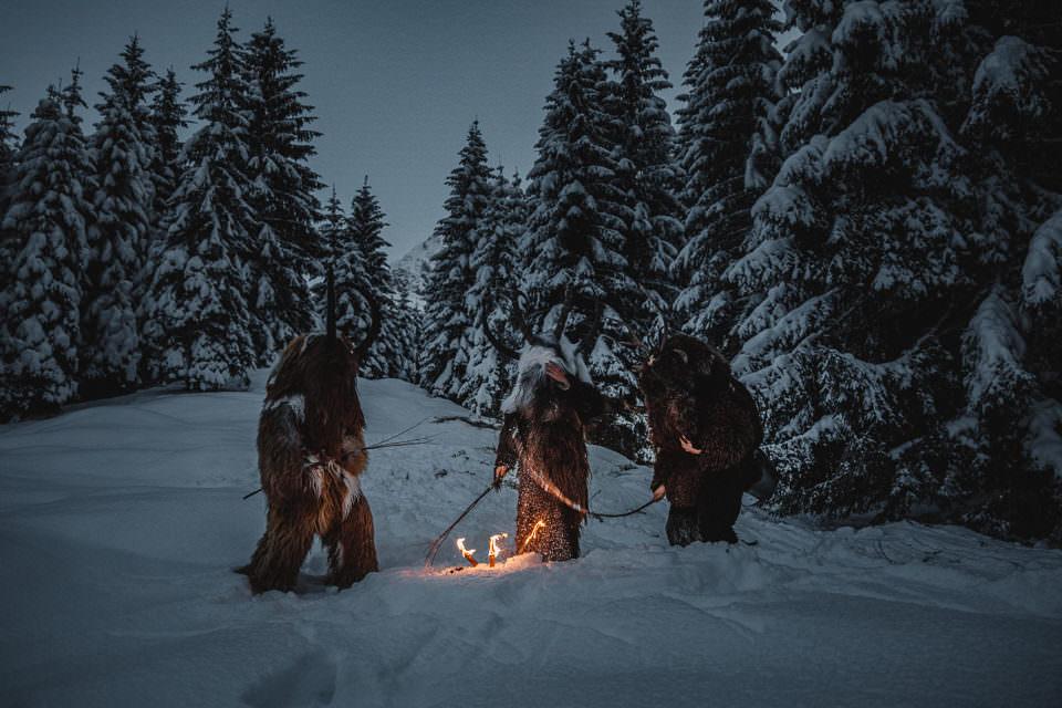 Als Krampus verkleidete Männer um ein Lagerfeuer