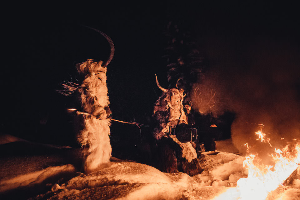 Als Krampusse verkleidete Männer um ein Lagerfeuer