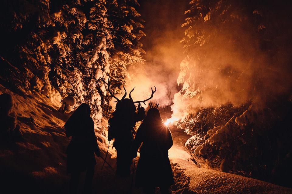Als Krampusse verkleidete Männer mit Feuer im winterlichen Wald