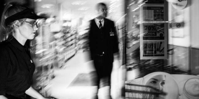 Eine Frau in schwarz gekleidet die einen Einkaufswagen schiebt. Dahinter ein verwischter Mann in Anzug.