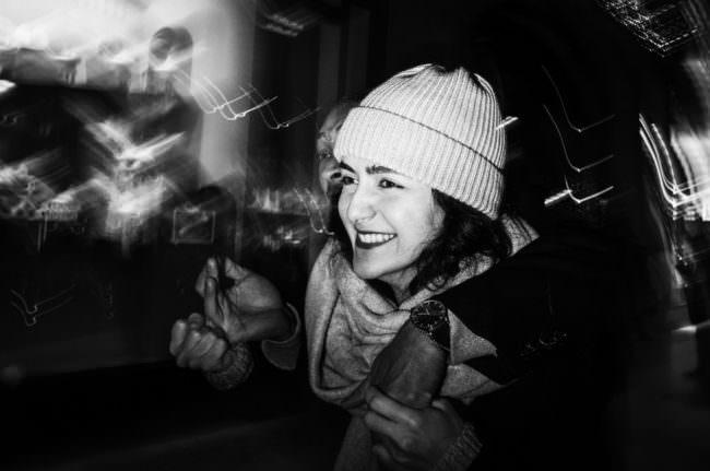Eine lachende junge Frau mit Mütze.
