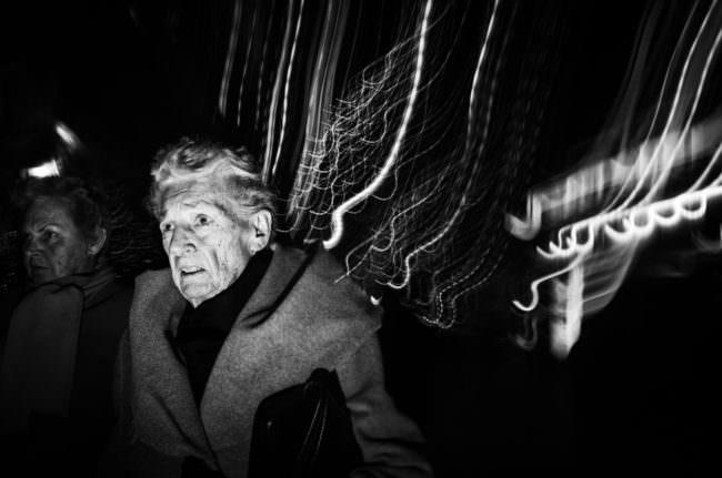 Ein älterer Mensch mit Lichtschlieren im Hintergrund.