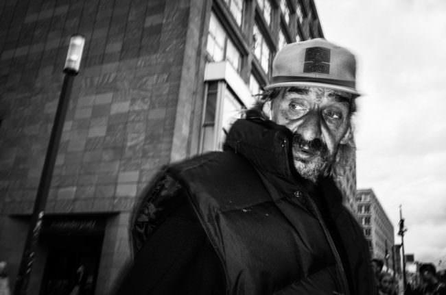 Mann mit Kappe vor einem Gebäude.