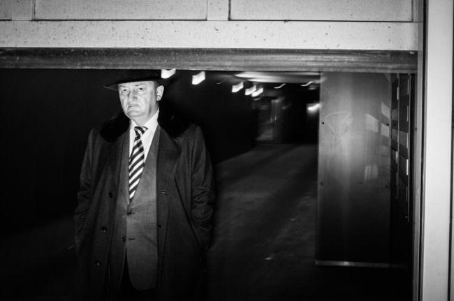 Mann mit Hut und gestreifter Krawatte sowie skeptischem Blick.