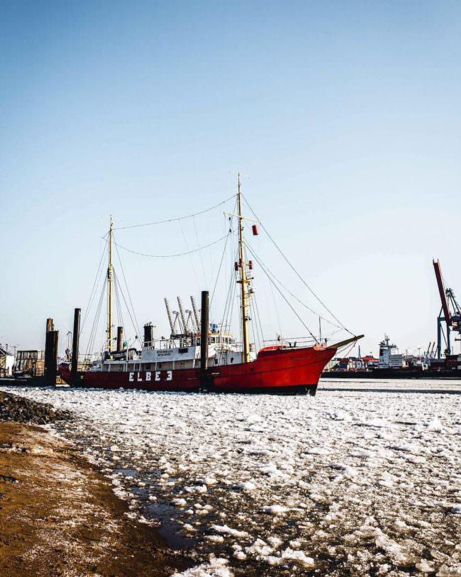 Ein Schiff auf einem verschneiten Fluss.