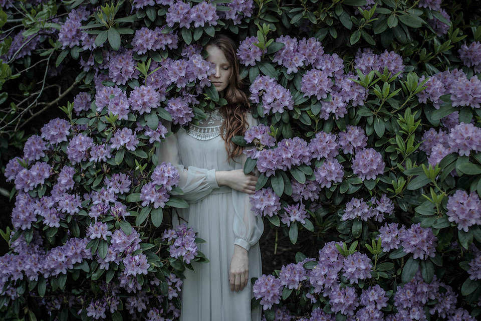 Frau in einem Busch mit lila Blüten