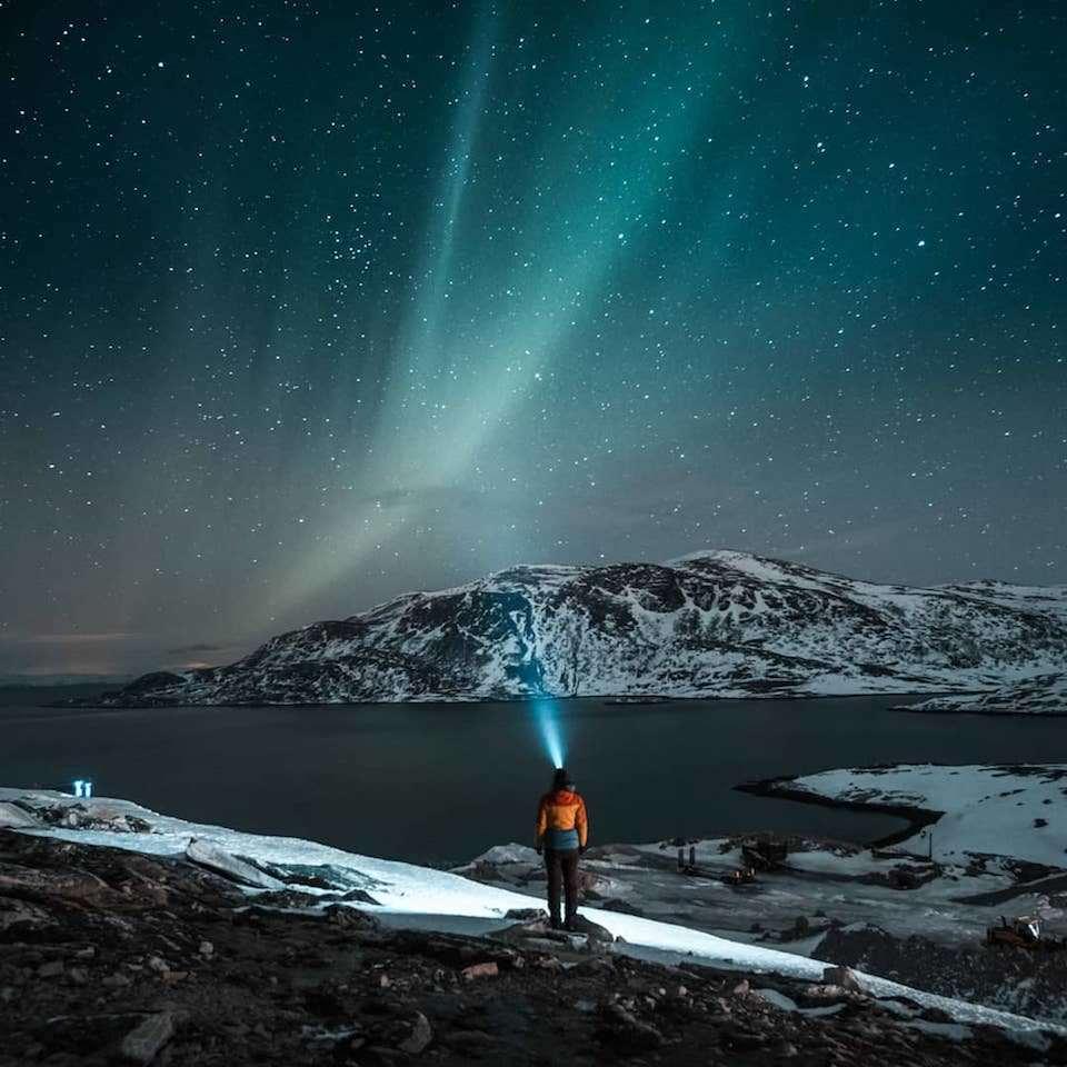 Ein Mensch mit einer Stirnlampe vor einer Berglandschaft unter Nordlichtern.
