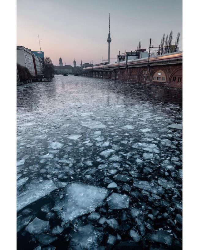 Ein zugefrorener Fluss neben einer Brücke.