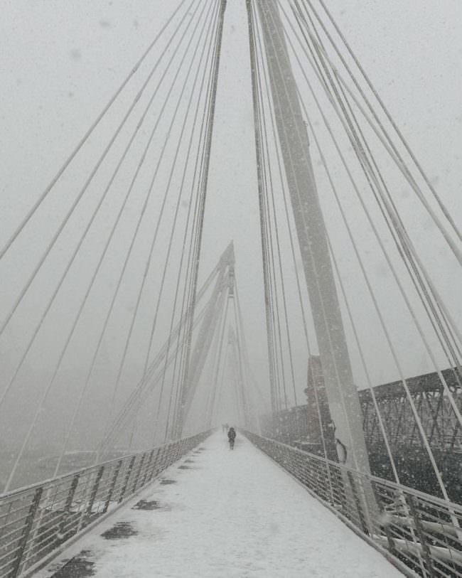 Eine verschneite Brücke über die eine Person läuft.