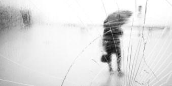 Person mit Regenschirm durch eine kaputte Glasscheibe