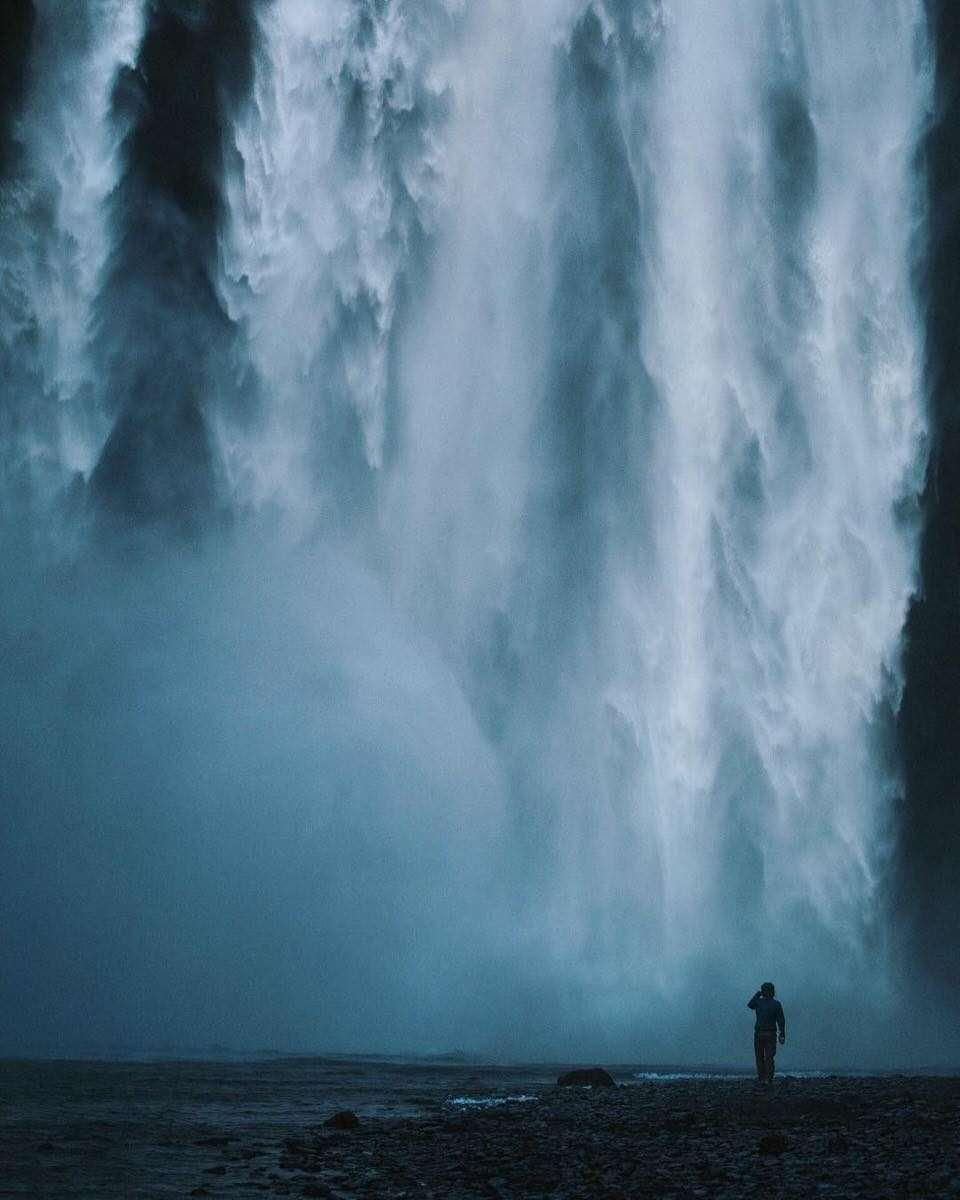 Eine Person vor einem Wasserfall