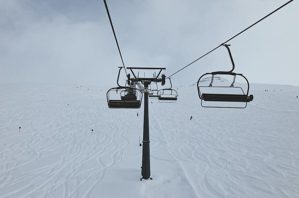Eine Sessellift, der ein Schneefeld hinauf führt.