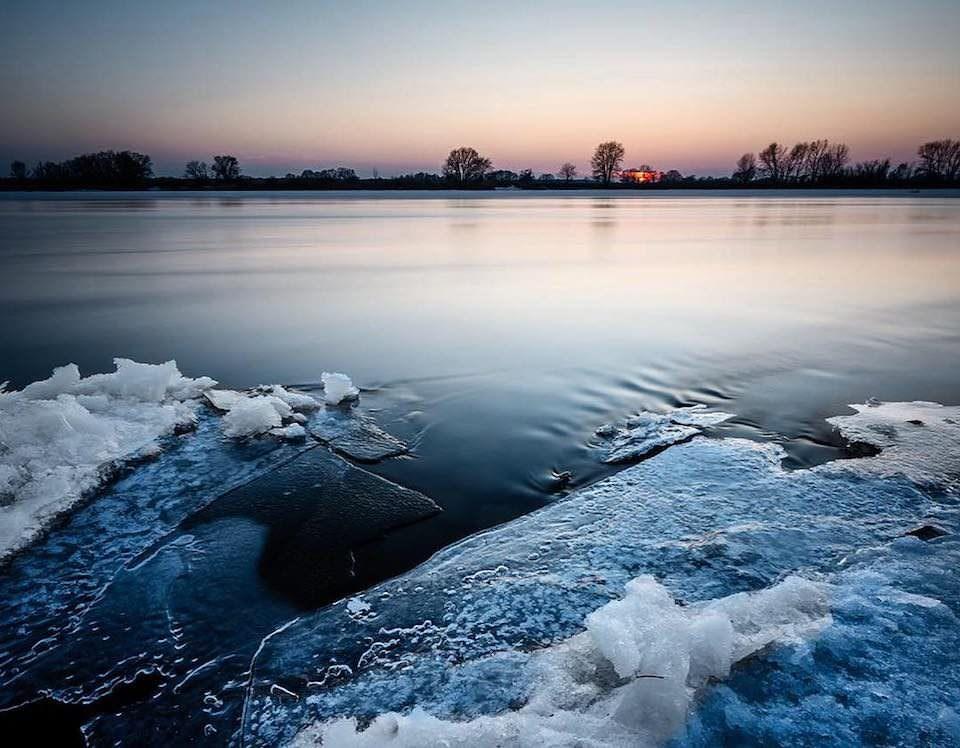 Das gefrorene Ufer eines Sees bei Sonnenuntergang.