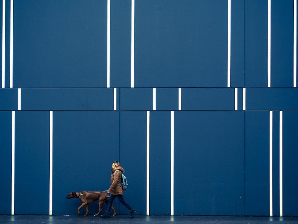 Eine Frau mit Hund vor einer blauen Wand