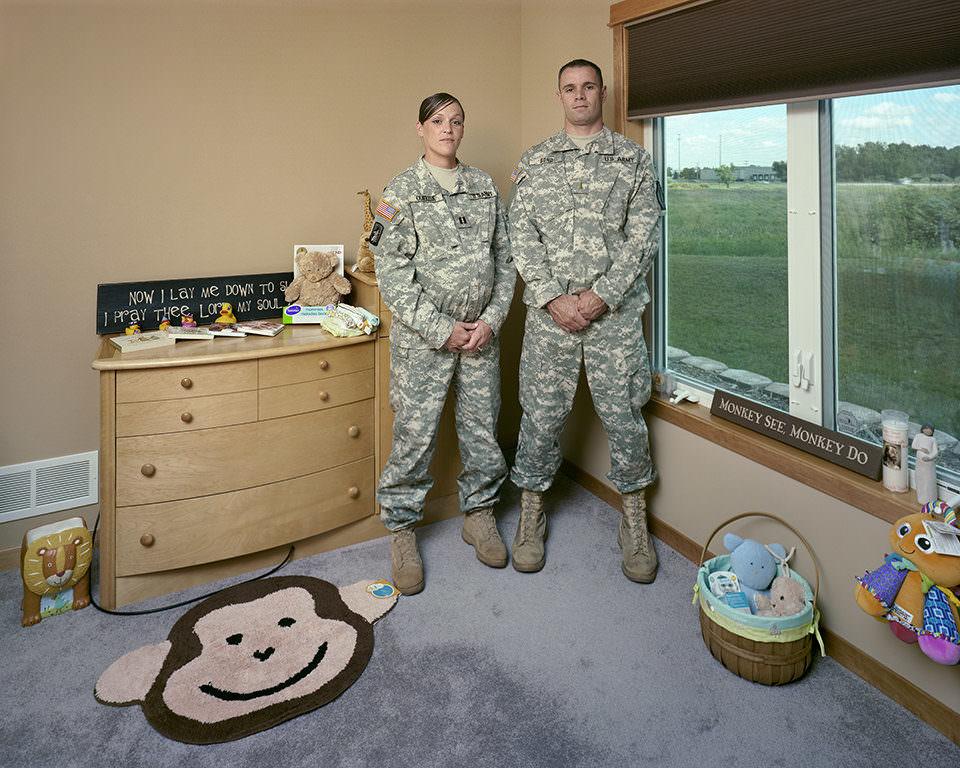 Ein Mann und eine schwangere Frau in Soldatenuniformen stehen in einem spartanisch möblierten Kinderzimmer.