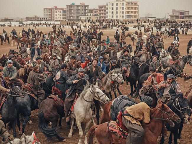 Menschen und Pferde auf einem staubigen Platz