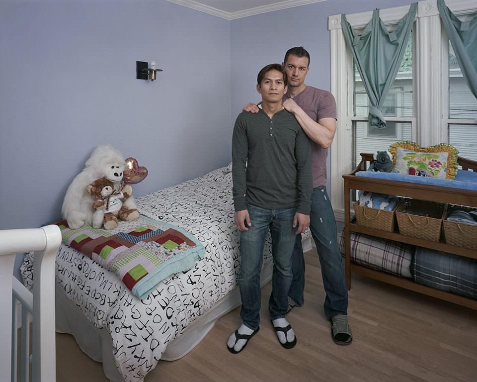 Zwei junge Männer stehen in einem Raum mit einem Einzelbett.
