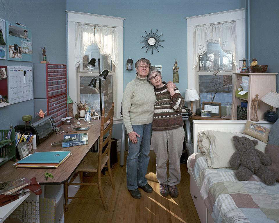 Zwei ältere Frauen stehen in einem Zimmer mit blauen Wänden.