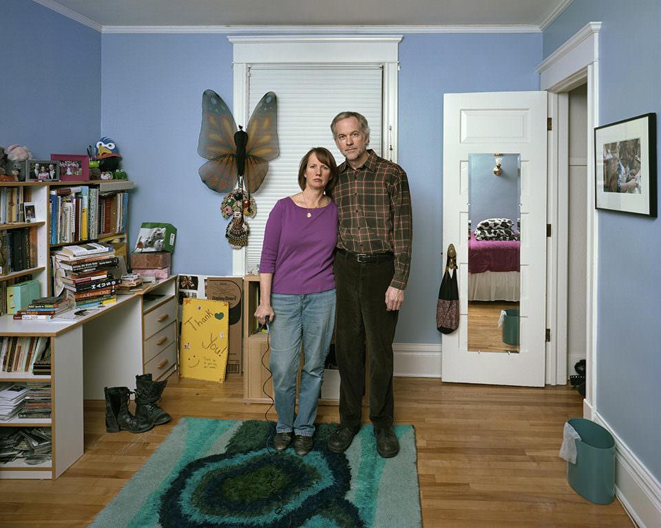 Eine Frau und ein Mann, die sich im Arm halten, stehen in einem Zimmer mit blauen Wänden.