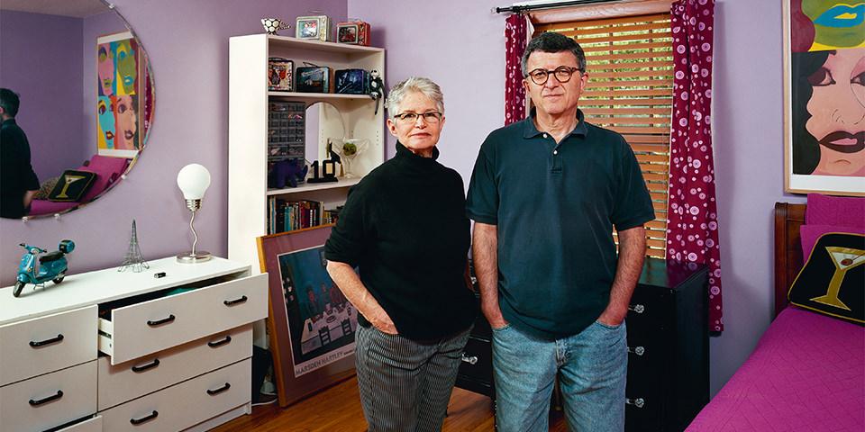 Ein Mann und eine Frau in einem Innenraum mit lila Wänden, Kommode, Schrank und Bett.