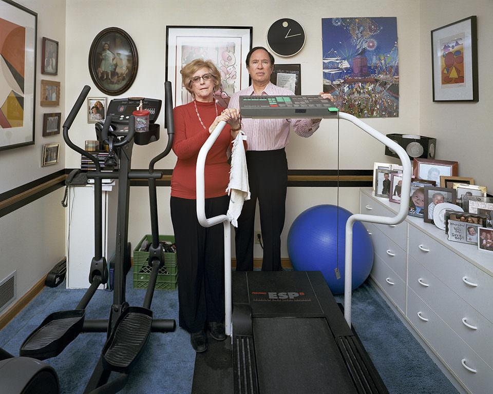 Ein älteres Paar steht in einem Zimmer mit Bildern an der Wand und zwei Sportgeräten mitten im Raum.