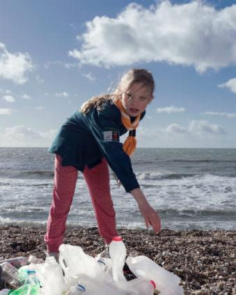 Mädchen mit Mülltüten am Strand