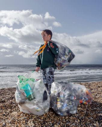 Junge mit Mülltüten am Strand