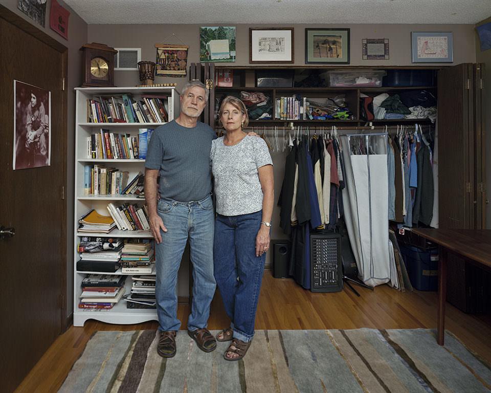 Ein Mann und eine Frau, die sich im Arm halten, stehen in einem Raum mit Kleiderständer und vollem Bücherregal.