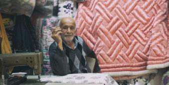 Rauchender Mann sitzt hinter einer Nähmaschine in einem kleinen Laden für Bettdecken.
