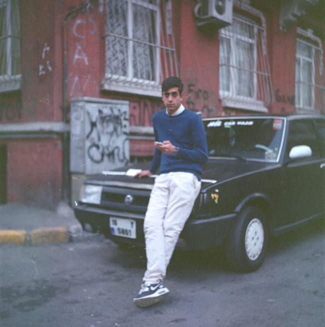 Ein junger Mann lehnt sich auf die Motorhaube eines Autos