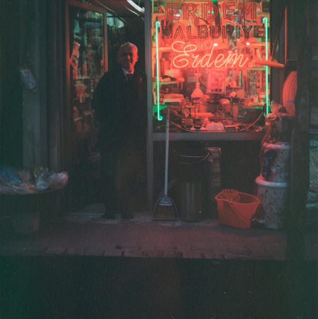 Ein Mann lehnt in der Tür zu einem rot beleuchteten Laden.